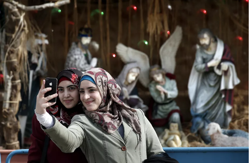 Muslim women take a selfie in front of a Christian mange